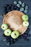 Old board, plums and apples background Stock Image