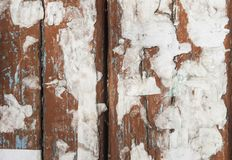 An old board, a wooden wall texture with paper ads. Wooden wall with scraps ads as a background royalty free stock photo