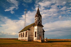An old boarded up church and a new radio tower Royalty Free Stock Photography