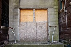 Old boarded up door to an abandoned business. Old boarded up double door to an abandoned business with rusting handrails outside royalty free stock image