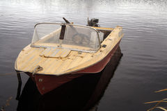 Old boat. The faulty old boat with the pendant boat motor is at a mooring stock photography