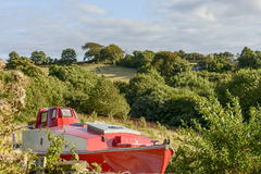 Old boat aground amid green country near Looe, Cornwall Stock Photo