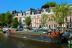 Old boat in Amsterdam channel with typical houses on the background, Amsterdam, Netherlands royalty free stock photo