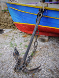 Old boat and anchor. Old fishing boat and a rusty old anchor stock photo