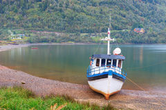Old boat anchored on the beach of the fjord of Puyuhuapi, Patago Stock Image