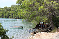 Old boat in bay under the pine-trees. Boats in azure sea, Croatia Royalty Free Stock Images