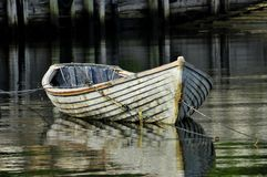Old Boat in the Bay. This old boat was tied up in some pretty still water,had a sense of the past Stock Photo