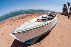 Old boat on the beach. Old weathered white boat on the egyptian beach Royalty Free Stock Photography