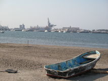 Old boat on beach. Scenic view of old boat on beach with city coastline in background, Veracruz, Mexico Stock Photography
