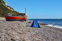 An old boat on the beach at Branscombe in Devon, England. Fishermen`s equipment stands in the foreground stock photo