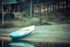Old boat on beach, lake, forest, Finland Royalty Free Stock Photos