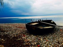 Old boat on the beach with perfect view by the lake. royalty free stock photos