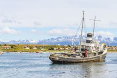 Old boat in Beagle channel with mountains and houses in Ushuaia. Patagonia, Argentina Royalty Free Stock Photos