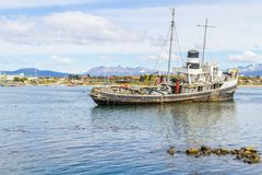 Old boat in Beagle channel with mountains and houses in Ushuaia. Patagonia, Argentina Royalty Free Stock Images