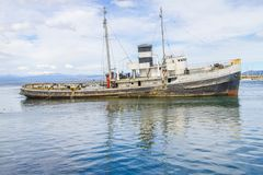 Old boat in Beagle channel with mountains in Ushuaia. Patagonia, Argentina Royalty Free Stock Images