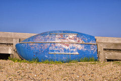 Old boat with blue hull resting on its side against sea wall. Old wooden boat on its side against a wooden sea barrier on a shingle beach. Blue sky background royalty free stock images