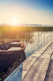 Old boat on the coast of lake at sunset Stock Photo