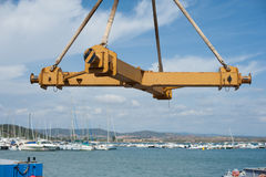 Old boat crane part with harbor in background. Old boat crane cross elevator part with harbor and boats out of focus in background Stock Photos