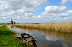 Old boat in a ditch in Holland. Typical landscape in Holland with an old boat in a ditch with a windmill, reeds and clouds Royalty Free Stock Image