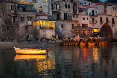 Old boat drifting in Cefalu harbor at dusk. Old boat drifting in a harbor of Cefalu at dusk, Sicily Stock Image