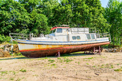Old boat on dry land. An old boat resting on support. Decay and rust. Forrest in background Stock Images