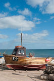 Old boat on dry land. SIDMOUTH, UK - AUGUST 30, 2007: Fishing boat by the sea front in this scenic coastal English town Stock Photography