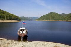 An old boat of the Fish Protection Inspectorate is moored at the reserved shore against the background of green hills.
