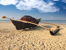 Old boat with fishing net on a sandy beach. India. Royalty Free Stock Photos
