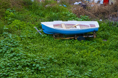 Old boat in a grass, old boat abandoned on the field Royalty Free Stock Image