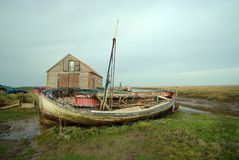 Old boat and historic barn. Royalty Free Stock Photos