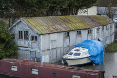 Old boat house. With boats moored alongside Stock Images