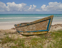 Old boat on Jamaican beach. Aged fishing row boat with peeling paint on a Jamaican beach Stock Image