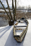 Old boat on  lake  coast  covered with snow in winter Royalty Free Stock Photos