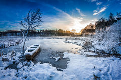 Old boat on the lake covered with snow in winter Royalty Free Stock Image