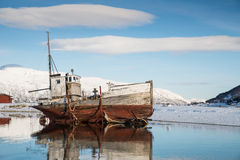Old boat on the lake. Near the mountains in winter Stock Photo
