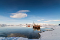 Old boat on the lake. Near the mountains in winter Royalty Free Stock Images