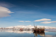 Old boat on the lake. Near the mountains in winter Stock Images