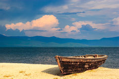 Old boat on the lake. Boat on the sandy shore of Lake Baikal royalty free stock images