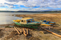 Old boat on lake shore Stock Photos