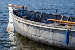 An old boat made of metal and rivets. The vessel is moored to th stock photo