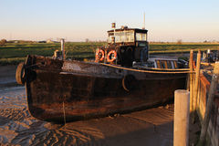 Old boat on mud bank. Old Grey metal boat on mud bank Stock Photo