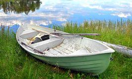 Old boat with oars on shore of lake. Finland Royalty Free Stock Images