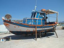 Old boat repaired. Old boat shored up on wooden sticks for repairs and new paint. Port in Malia, Crete, Greece Stock Image