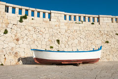 Old boat resting on harbor wall Stock Photos