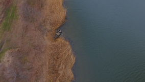 Old boat on the river bank in spring time. Aerial view stock footage