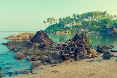 Old boat in the rocks at the beach of Goa. Tinted Royalty Free Stock Photo