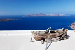Old boat on the roof of the building on Santorini island, Greece. View on Caldera and Aegean sea, sunny day, blue sky Stock Images