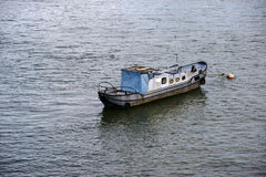 The old boat. An old boat with rusted side walls and a covered cabin anchored on the banks of a river Stock Image