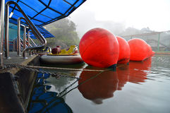 Old boat and safety ballon. With pedal boat and fog as a backgroud Stock Images