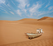Old boat among the sand dunes in the desert Royalty Free Stock Photo